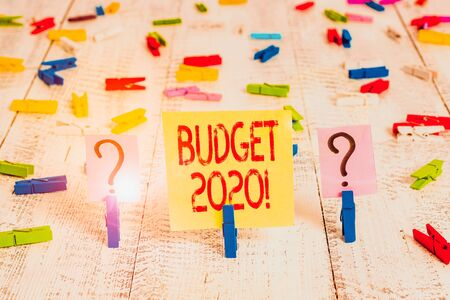 Writing note showing Budget 2020. Business concept for estimate of income and expenditure for next or current year Crumbling sheet with paper clips placed on the wooden table Foto de archivo - 138299622