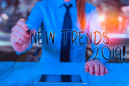 Text sign showing New Trends 2019. Business photo text general direction in which something is developing Female business person sitting by table and holding mobile phone