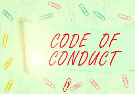 Text sign showing Code Of Conduct. Business photo text Ethics rules moral codes ethical principles values respect Paper clip and torn cardboard placed above a plain pastel table backdrop Stock Photo