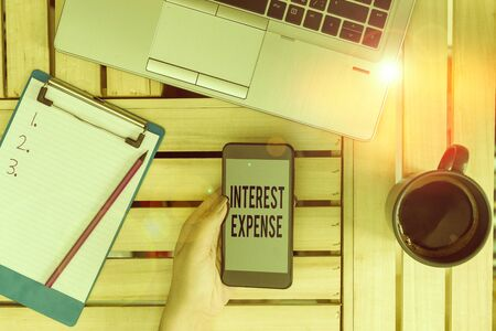 Text sign showing Interest Expense. Business photo text cost of debt that has occurred during a period of time woman computer smartphone drink mug office supplies technological devices Reklamní fotografie