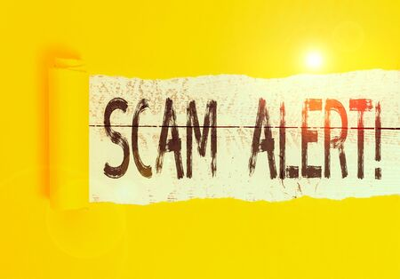 Text sign showing Scam Alert. Business photo text fraudulently obtain money from victim by persuading him Cardboard which is torn in the middle placed above a wooden classic table