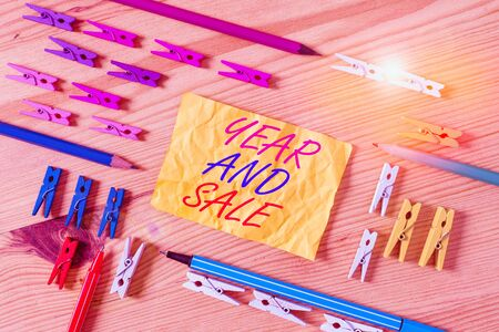 Text sign showing Year And Sale. Business photo showcasing Annual Discounts Holiday Season clearance Traditional Colored clothespin papers empty reminder wooden floor background office Stock Photo