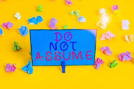 Text sign showing Do Not Assume. Business photo showcasing Ask first to avoid misunderstandings confusion problems Colored crumpled papers empty reminder white floor background clothespin Foto de archivo