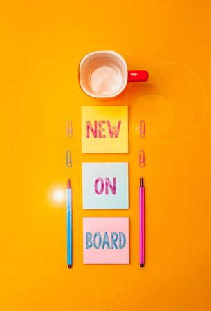 Text sign showing New On Board. Business photo text Welcome to the team Adaptation Collaboration Someone hired Coffee cup blank colored sticky note two ballpoints clips yolk background