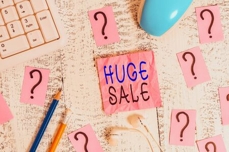 Conceptual hand writing showing Huge Sale. Concept meaning putting products on high discount Great price Black Friday Writing tools and scribbled paper on top of the wooden table Standard-Bild