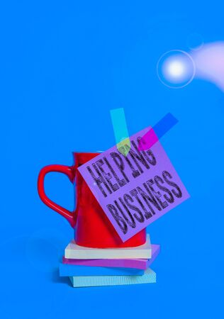 Writing note showing Helping Business. Business concept for improving some measure of an enterprise s is success Cup colored sticky note banners stacked pads lying pastel background