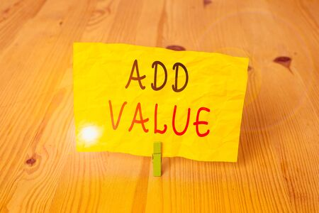 Conceptual hand writing showing Add Value. Concept meaning an improvement or addition to something that makes it worth more Wooden floor background green clothespin groove slot office