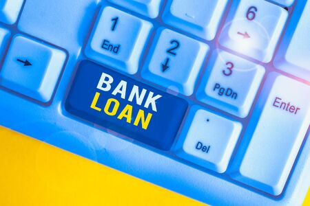 Text sign showing Bank Loan. Business photo text an amount of money loaned at interest by a bank to a borrower White pc keyboard with empty note paper above white background key copy space Stock Photo