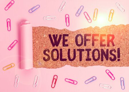 Conceptual hand writing showing We Offer Solutions. Concept meaning way to solve problem or deal with difficult situation Paper clip and torn cardboard on wood classic table backdrop