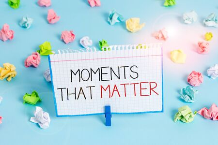 Handwriting text Moments That Matter. Conceptual photo Meaningful positive happy memorable important times Colored crumpled papers empty reminder blue floor background clothespin