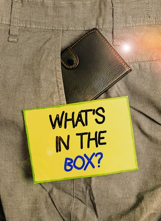 Handwriting text writing What s is In The Box question. Conceptual photo Curapp storeity Opening a gift Surprise package Small little wallet inside man trousers front pocket near notation paper Foto de archivo - 138473014