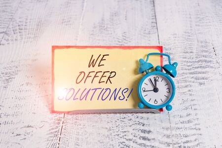Writing note showing We Offer Solutions. Business concept for Offering help assistance Experts advice strategies ideas Alarm clock tilted above buffer wire in front of notepaper