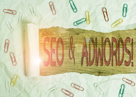 Handwriting text Seo And Adwords. Conceptual photo they are main tools components of Search Engine Marketing Paper clip and torn cardboard placed above a wooden classic table backdrop
