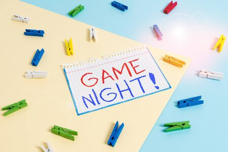 Writing note showing Game Night. Business concept for usually its called on adult play dates like poker with friends Colored clothespin paper reminder with yellow blue background