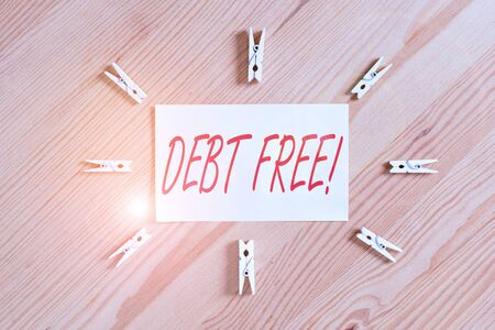 Text sign showing Debt Free. Business photo showcasing does not owning any money to any individual or companies Colored clothespin papers empty reminder wooden floor background office