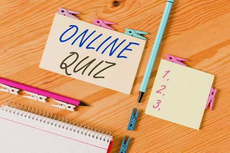 Conceptual hand writing showing Online Quiz. Concept meaning game or a mind sport that are published on the Internet Colored crumpled papers wooden floor background clothespin Zdjęcie Seryjne