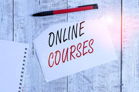 Writing note showing Online Courses. Business concept for courses deliver a series of lessons to a web browser Torn paper and notebook sheet with a pen placed on top of wooden table Zdjęcie Seryjne