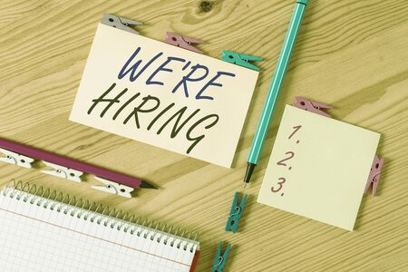 Conceptual hand writing showing We Re Hiring. Concept meaning process of reviewing applications and finding candidates Colored crumpled papers wooden floor background clothespin