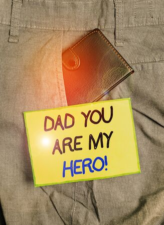 Handwriting text writing Dad You Are My Hero. Conceptual photo Admiration for your father love feelings compliment Small little wallet inside man trousers front pocket near notation paper