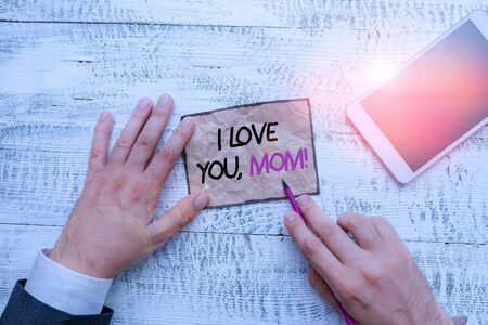 Word writing text I Love You, Mom. Business photo showcasing Loving message emotional feelings affection warm declaration Hand hold note paper near writing equipment and modern smartphone device