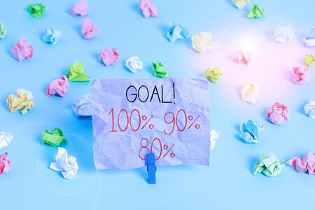 Writing note showing Goal 100 90 80. Business concept for Percentage of your objectives fulfilment success level Colored crumpled papers empty reminder blue floor background clothespin