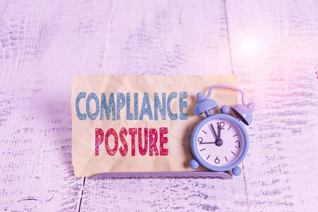 Word writing text Compliance Posture. Business photo showcasing analysisage the defense of enterprise and assure resources Mini blue alarm clock stand tilted above buffer wire in front of notepaper