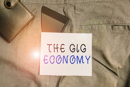Conceptual hand writing showing The Gig Economy. Concept meaning Market of Shortterm contracts freelance work temporary Smartphone device inside trousers front pocket with wallet