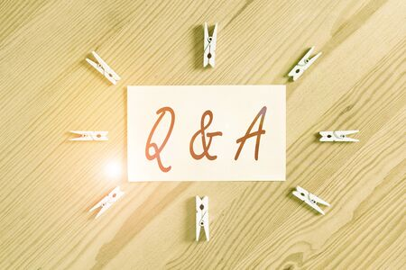 Text sign showing Q And A. Business photo showcasing defined as questions being asked and answers Colored clothespin papers empty reminder wooden floor background office