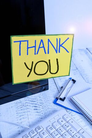 Word writing text Thank You. Business photo showcasing polite expression used when acknowledging gift service compliment Note paper taped to black computer screen near keyboard and stationary