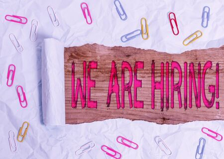 Handwriting text We Are Hiring. Conceptual photo recently you employ someone or pay someone to do particular job Paper clip and torn cardboard placed above a wooden classic table backdrop