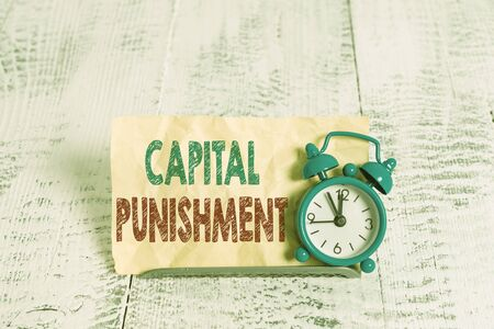 Word writing text Capital Punishment. Business photo showcasing authorized killing of someone as punishment for a crime Mini blue alarm clock stand tilted above buffer wire in front of notepaper