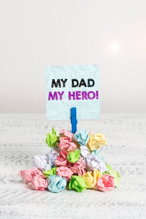 Handwriting text My Dad My Hero. Conceptual photo Admiration for your father love feelings emotions compliment Reminder pile colored crumpled paper clothespin reminder white wooden space