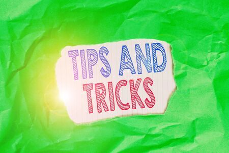 Writing note showing Tips And Tricks. Business concept for piece of inside facts specially in betting or investing Green crumpled colored paper sheet torn colorful background