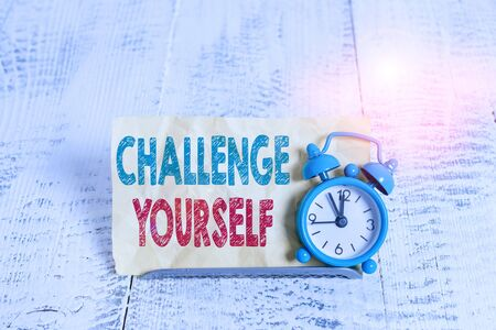 Word writing text Challenge Yourself. Business photo showcasing opportunity to be part of something bigger than ourselves Mini blue alarm clock stand tilted above buffer wire in front of notepaper
