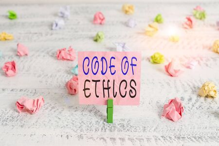 Handwriting text Code Of Ethics. Conceptual photo basic guide for professional conduct and imposes duties Green clothespin white wood background colored paper reminder office supply
