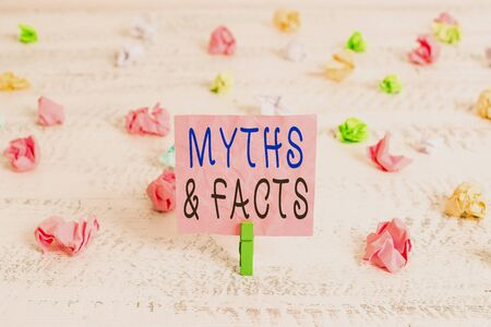 Handwriting text Myths And Facts. Conceptual photo usually traditional story of ostensibly historical events Green clothespin white wood background colored paper reminder office supply