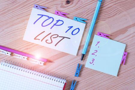 Conceptual hand writing showing Top 10 List. Concept meaning the ten most important or successful items in a particular list Colored crumpled papers wooden floor background clothespin Archivio Fotografico