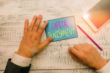 Word writing text Capital Punishment. Business photo showcasing authorized killing of someone as punishment for a crime Hand hold note paper near writing equipment and modern smartphone device