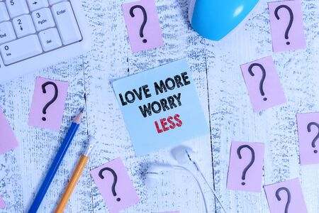 Conceptual hand writing showing Love More Worry Less. Concept meaning Have a good attitude motivation be lovable enjoy life Writing tools and scribbled paper on top of the wooden table