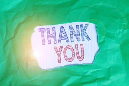 Writing note showing Thank You. Business concept for polite expression used when acknowledging gift service compliment Green crumpled colored paper sheet torn colorful background