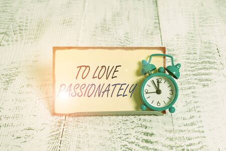 Writing note showing To Love Passionately. Business concept for Strong feeling for someone or something else Affection Alarm clock tilted above buffer wire in front of notepaper