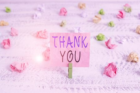 Handwriting text Thank You. Conceptual photo polite expression used when acknowledging gift service compliment Green clothespin white wood background colored paper reminder office supply Banco de Imagens