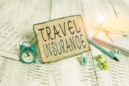 Writing note showing Travel Insurance. Business concept for covers the costs and losses associated with traveling Notepaper on wire in between computer keyboard and sheets