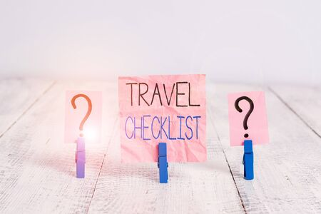 Handwriting text Travel Checklist. Conceptual photo a list of things to be checked or done for the planned trip Scribbled and crumbling sheet with paper clips placed on the wooden table