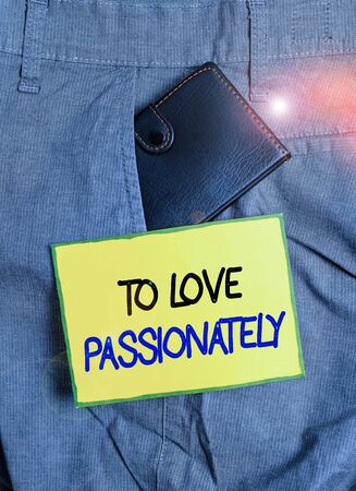 Handwriting text writing To Love Passionately. Conceptual photo Strong feeling for someone or something else Affection Small little wallet inside man trousers front pocket near notation paper