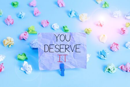 Writing note showing You Deserve It. Business concept for Reward for something well done Deserve Recognition award Colored crumpled papers empty reminder blue floor background clothespin Stock Photo