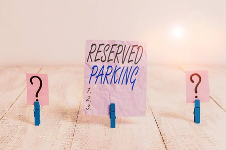 Text sign showing Reserved Parking. Business photo showcasing parking spaces that are reserved for specific individuals Scribbled and crumbling sheet with paper clips placed on the wooden table
