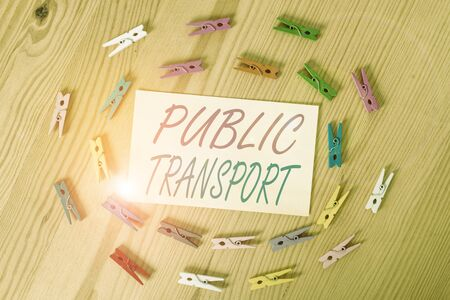 Text sign showing Public Transport. Business photo showcasing transport of passengers by group travel systems to public Colored clothespin papers empty reminder wooden floor background office