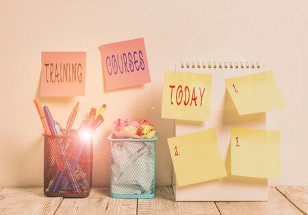Word writing text Training Courses. Business photo showcasing lessons to teach the skills and knowledge for a job 6 Sticky Notes on Wall Open Spiral Notebook 2 Pencil Pots on Work Desk