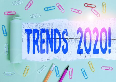 Handwriting text writing Trends 2020. Conceptual photo general direction in which something is developing or changing Stationary and torn cardboard placed above a wooden classic table backdrop